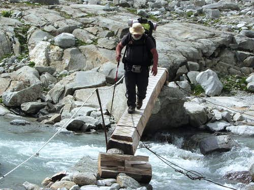 A heavily loaded long distance hiker crossing a stream on the Neveser Höhenweg