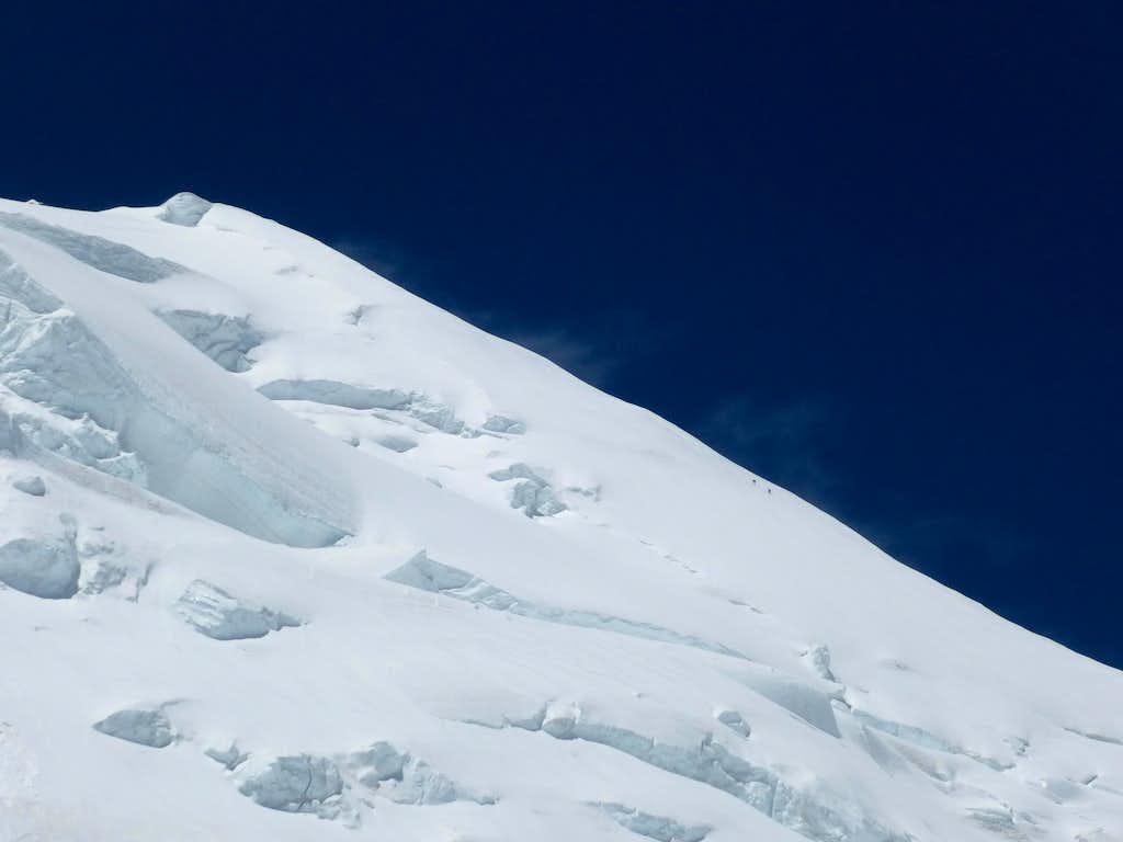 2 Sherpas dwarfed by the Kun summit ridge