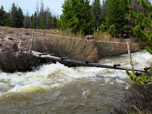 Flooded creek with a precarious bridge, seen on the trail to Dollar Lake, the base camp for Kings Peak, Uinta Range, Utah