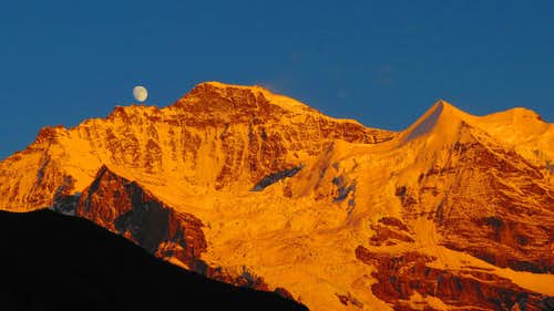 Moon grows up during Alpenglühen at Jungfrau summit